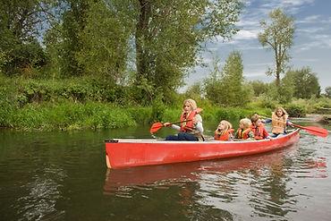 Children canoeing wearing life vests.
