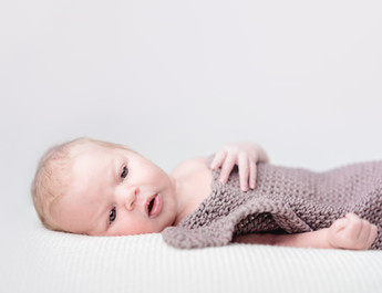 Baby mit grauer Decke