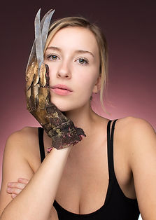A young whit lady on a pink backdrop wearing a freddy kruger glove. Her non chalant stare makes this a very unique and captivating photo.