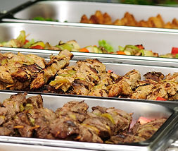 Assortment of food in catering trays.