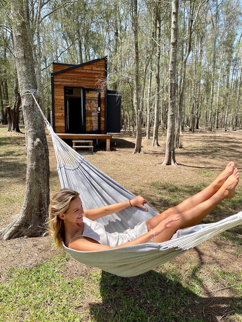 Hauslein Tiny House Co. girl on a hammock simplifying life living in a tiny house, tiny house featured on Brilliant-Online magazine