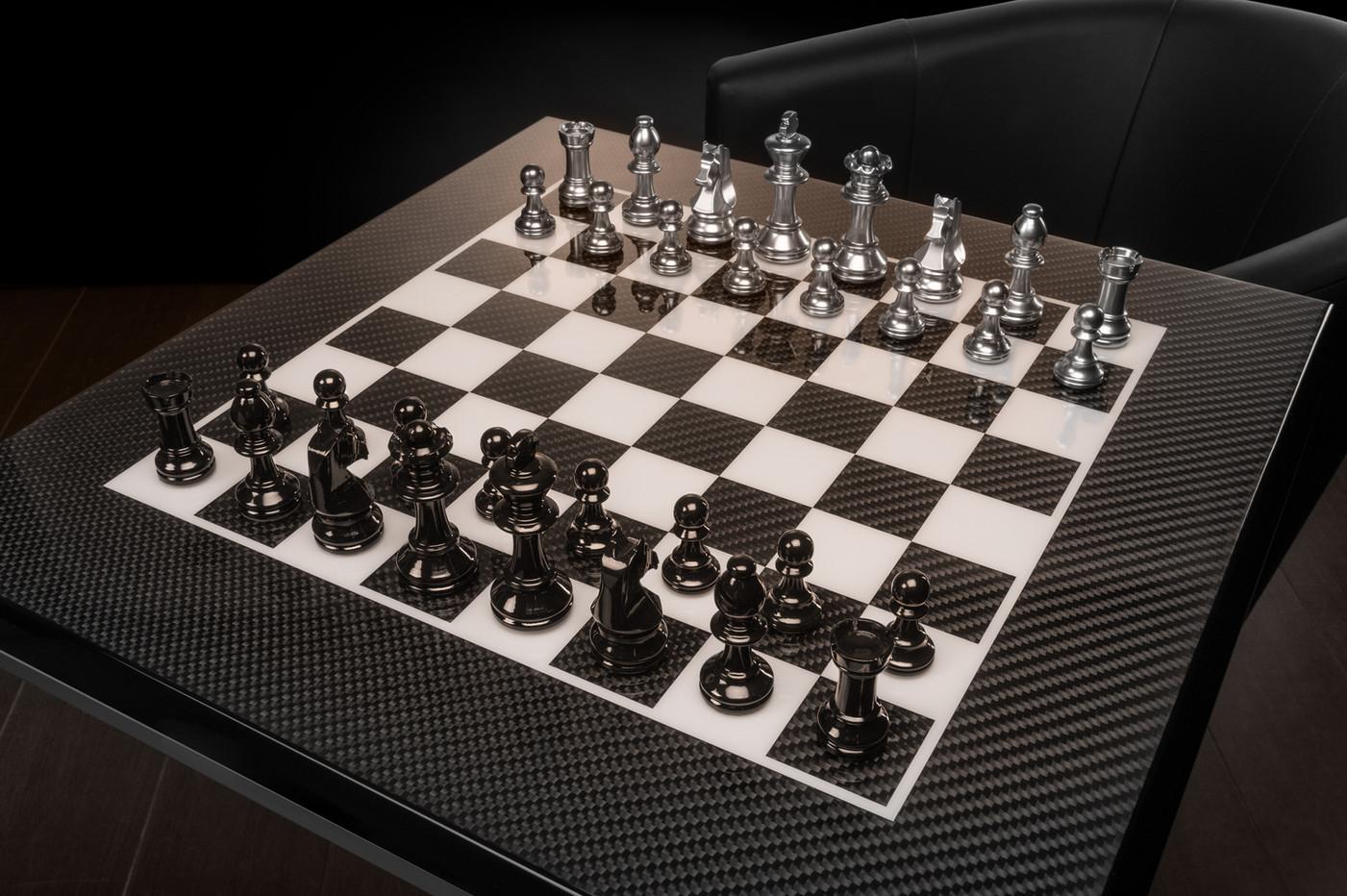 Table d'échecs  Plateau de jeu 60x60cm en fibre de carbone sergé 600g, 32 pions noir brillant / chrome vernis.  Piètement en métal noir brillant avec revêtement epoxy.  Plaquette d'identification en aluminium.  Finitions faites avec un vernis polyuréthane poli-lustré avec traitement céramique anti rayures.      Tarif : 4000€
