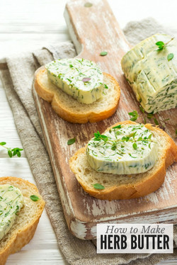 Garlic and herb butter slices on baguette slices on a cutting board
