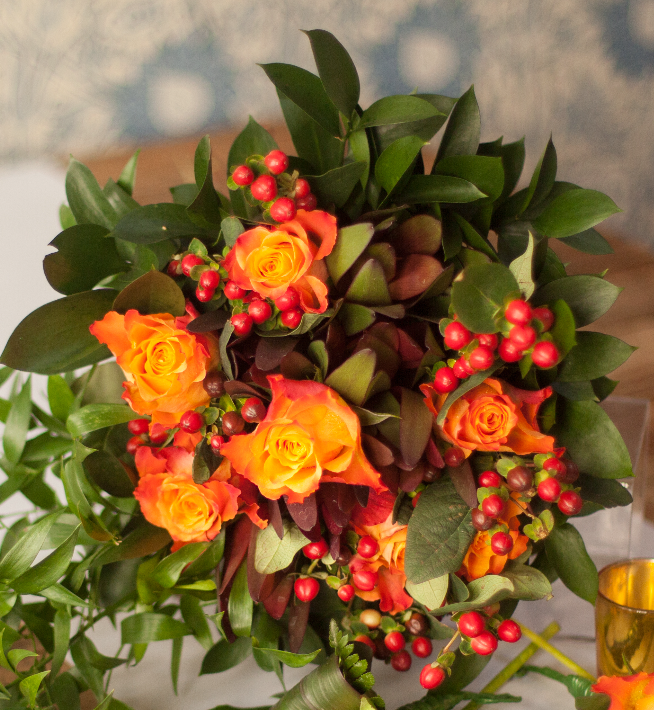 Christmas Bouquet containing leucadendron safari sunset, flame coloured roses and hypericum