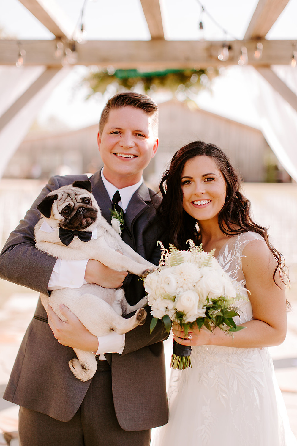 Bride and Groom getting a picture with their dog on their wedding day.