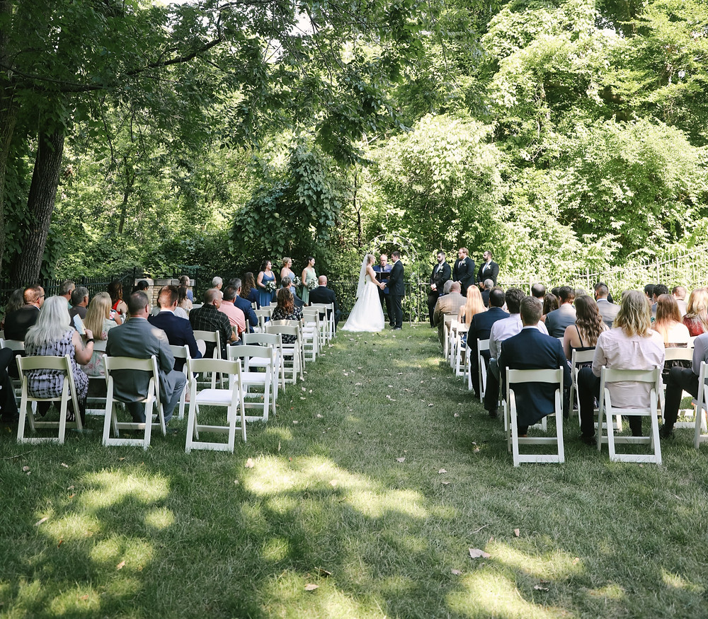 Wedding ceremony under a very green forest type area.