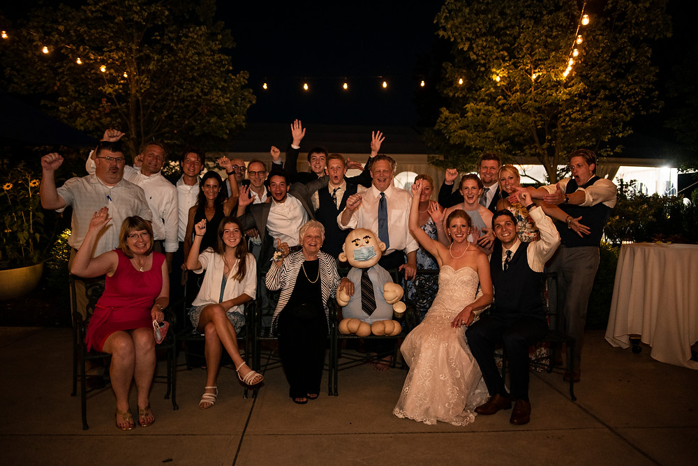 Couple who was just married, take a picture with many of their guests near the end of their wedding reception.
