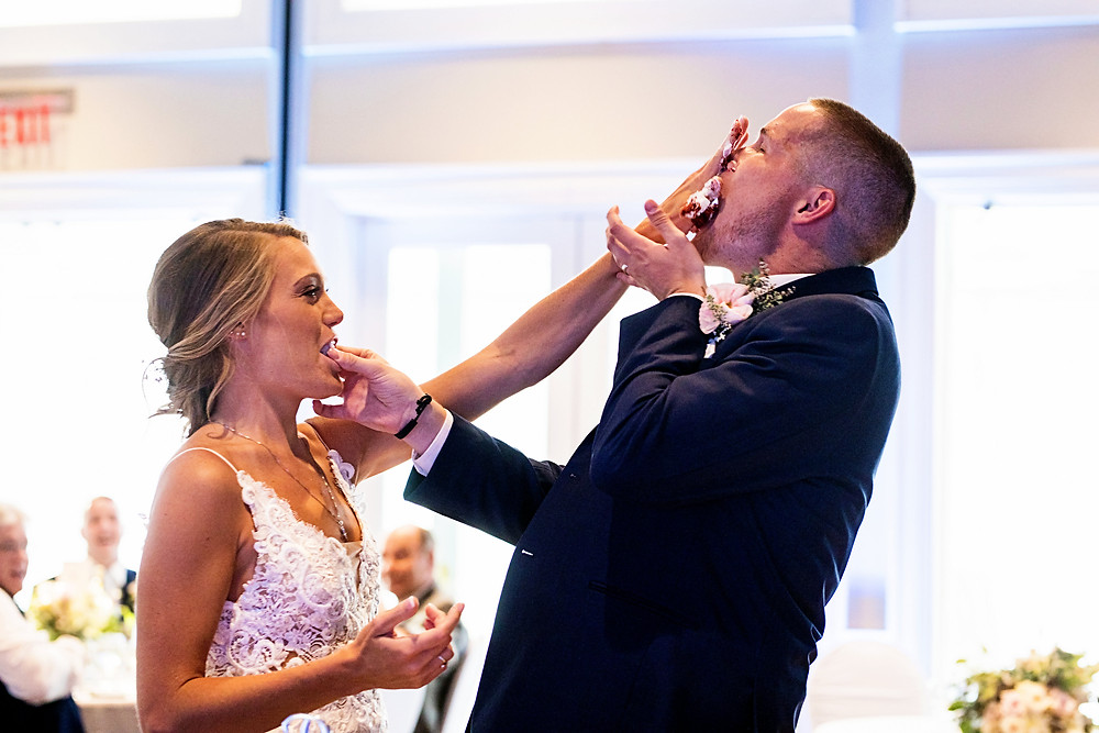 Bride smashing cake in the groom's face.
