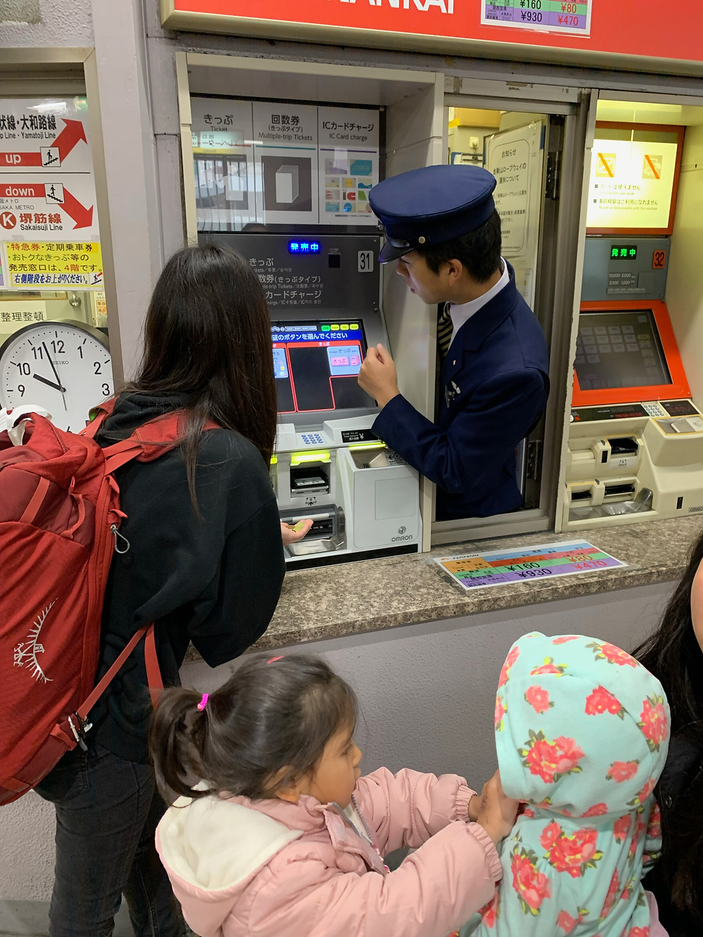 Woman and children purchasing train tickets with attendant in Japan