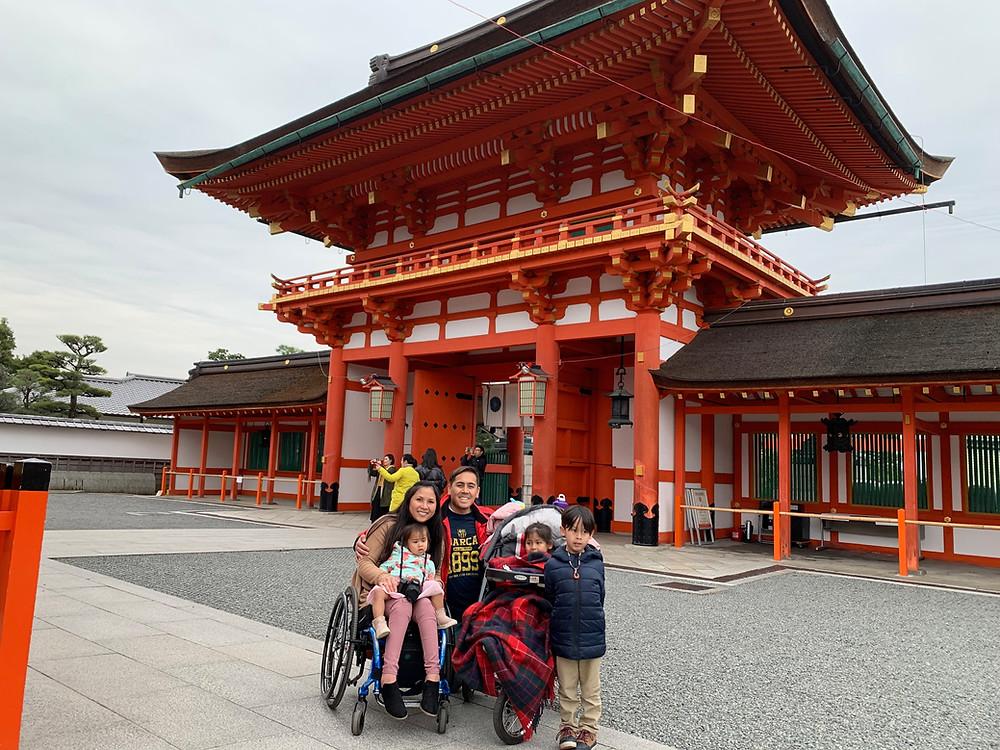 Asian Family At the entrance of the Fushimi Inari Shrine in Kyoto, Japan