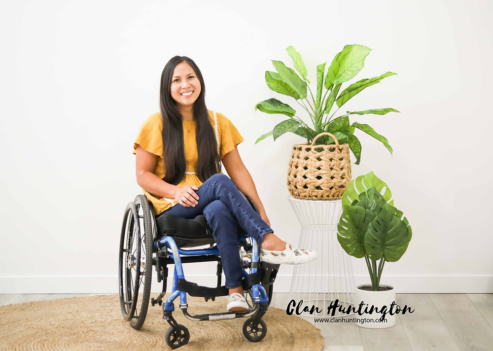 Asian woman in a wheelchair wearing yellow next to plants