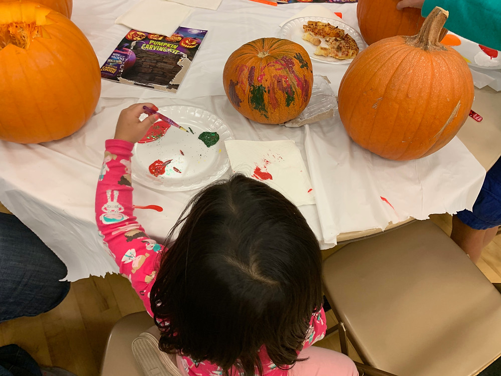 Picture of child painting pumpkins for Halloween.