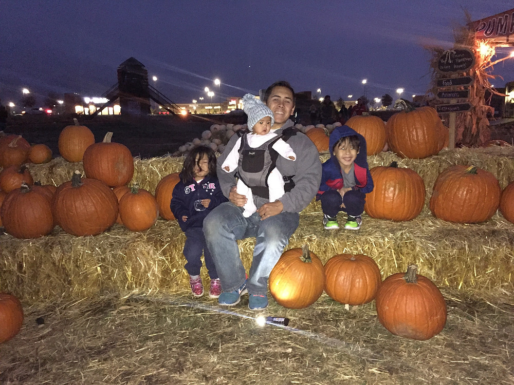 Picture of dad and children at Jaker's Jack-O-Lantern in Springville, UT surrounded by pumpkins.