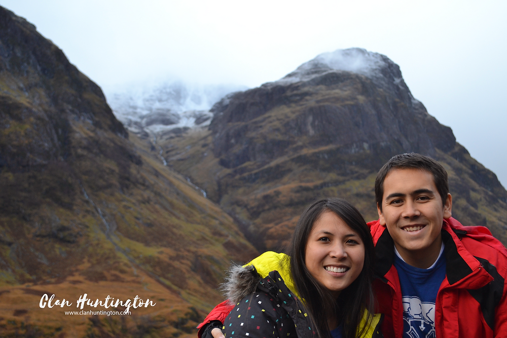 Asian man and woman in front of Glencoe in the Scottish Highlands in fall