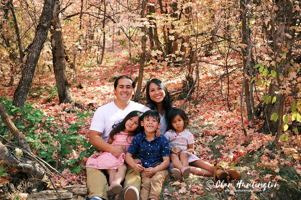 Asian family sitting together among fall, autumn leaves in Utah forest.