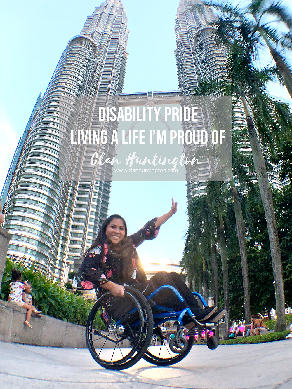 Asian woman in a wheelchair, traveling, doing wheelies in front of Towers in Malaysia