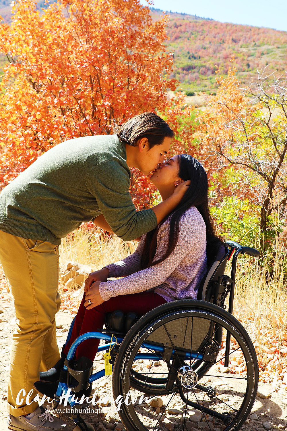Asian man leaning over to kiss woman in a wheelchair against fall colors in Utah.