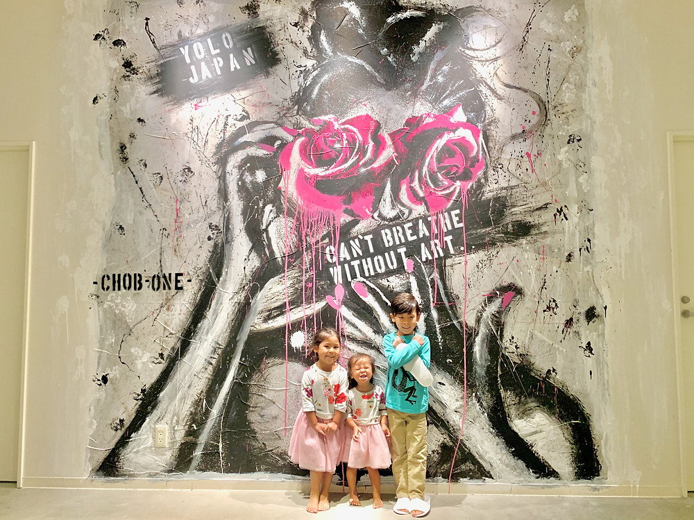 Children in front of a modern abstract art piece in Japan