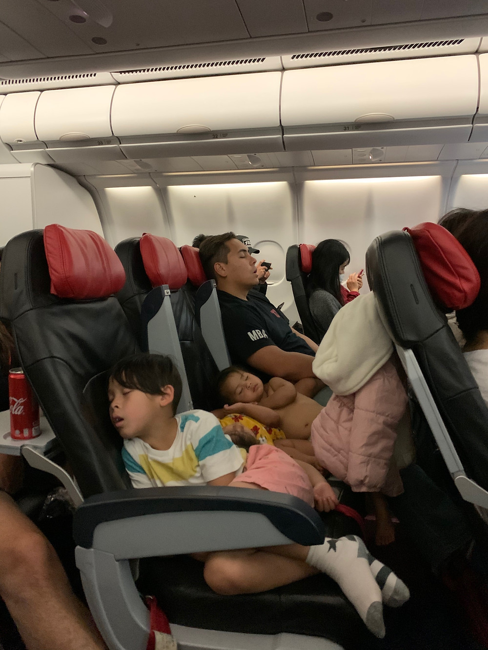 Children and dad sleep on airplane during very long flight.