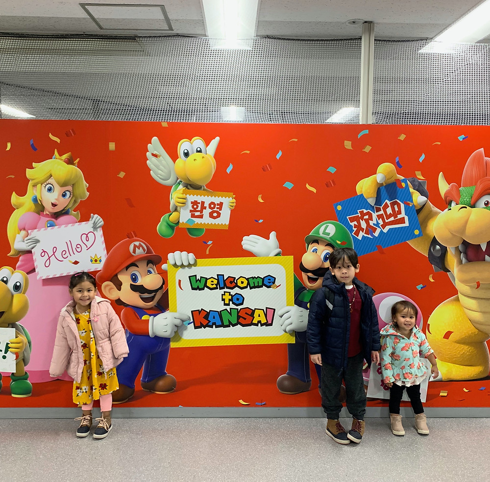 Children in front of a big mario sign in the Osaka Kansai Airport in Japan.