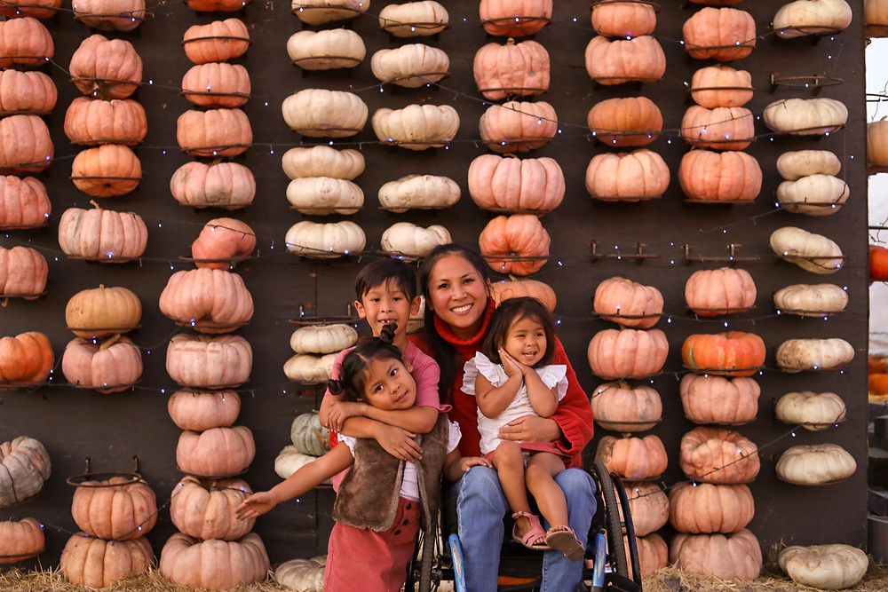 Picture of mom in a wheelchair with children in front of a pumpkin mural wall.