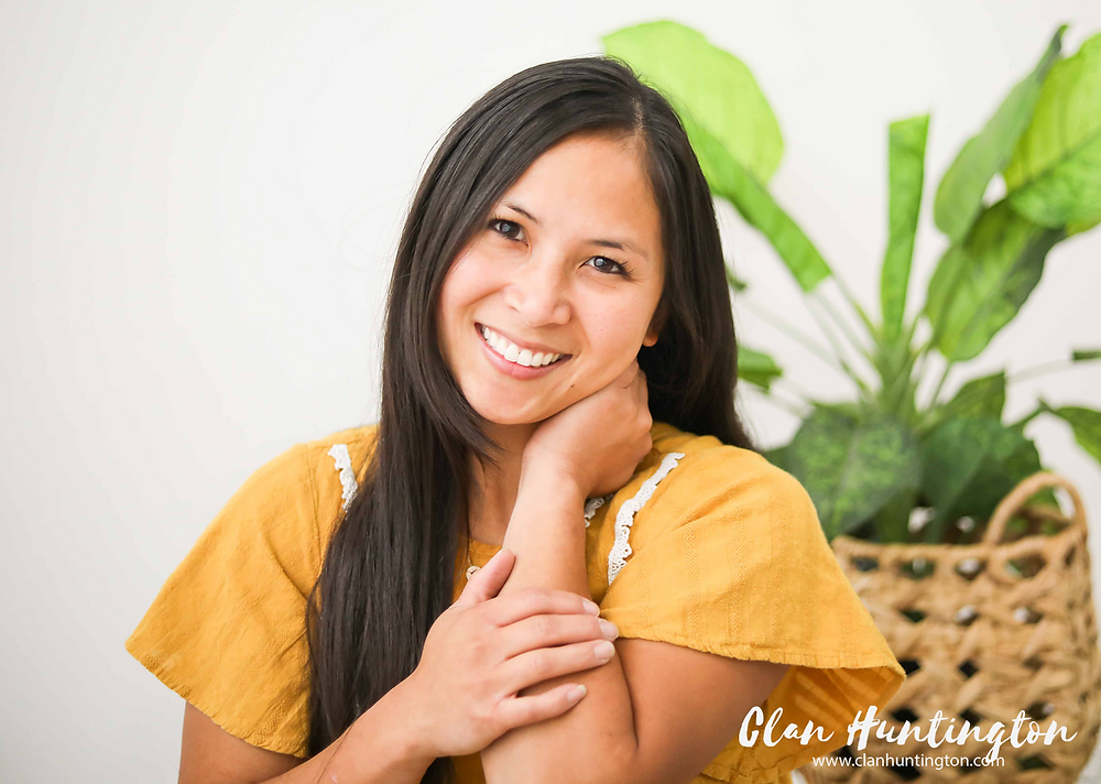 Asian woman in yellow smiling against white backdrop and plants. Talking about self care.
