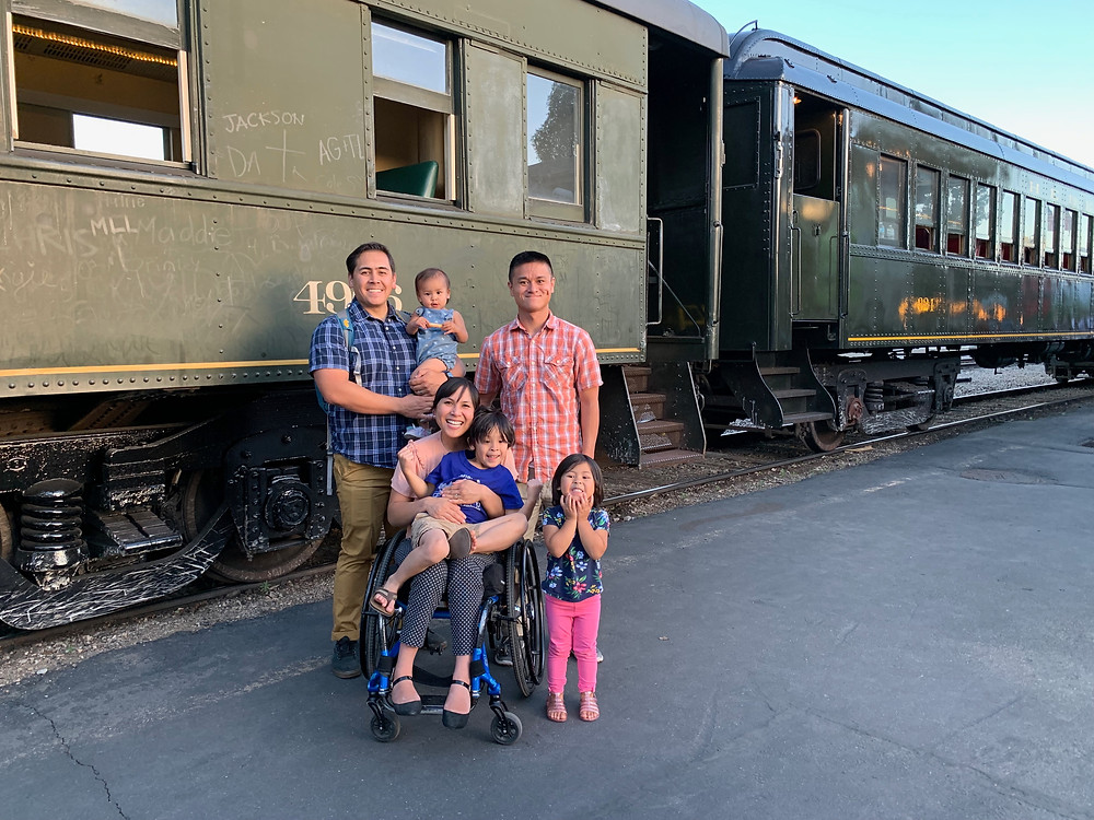 Asian family in front of vintage train in Heber City, UT.