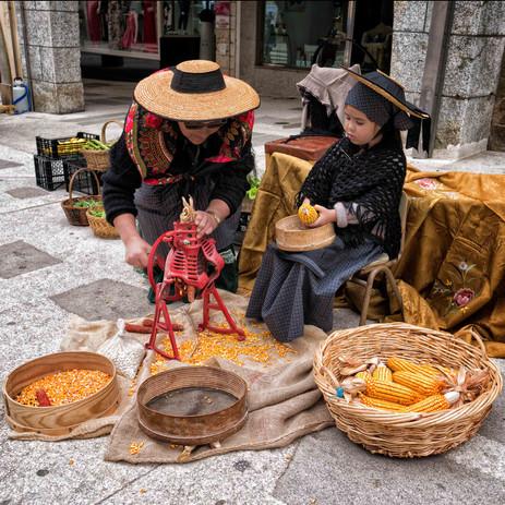 Abuela y nieta desgranando manualmente el maíz con sus trajes típicos...