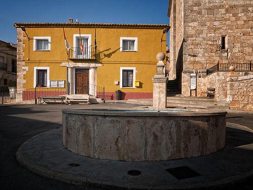 Pilón en la plaza de Horcajada de la Torre (Cuenca) al fondo el ayuntamiento.