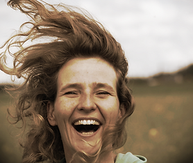 Gezicht van lachende Dagmar de shiatsutherapeute met haar in de wind