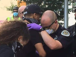 Police officer prays with protester in 'touching' photo and video.