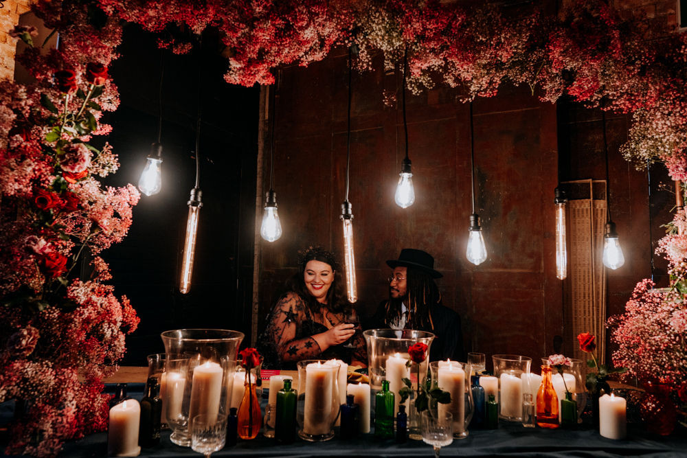 pink floral arch, industrial lights and gothic candles