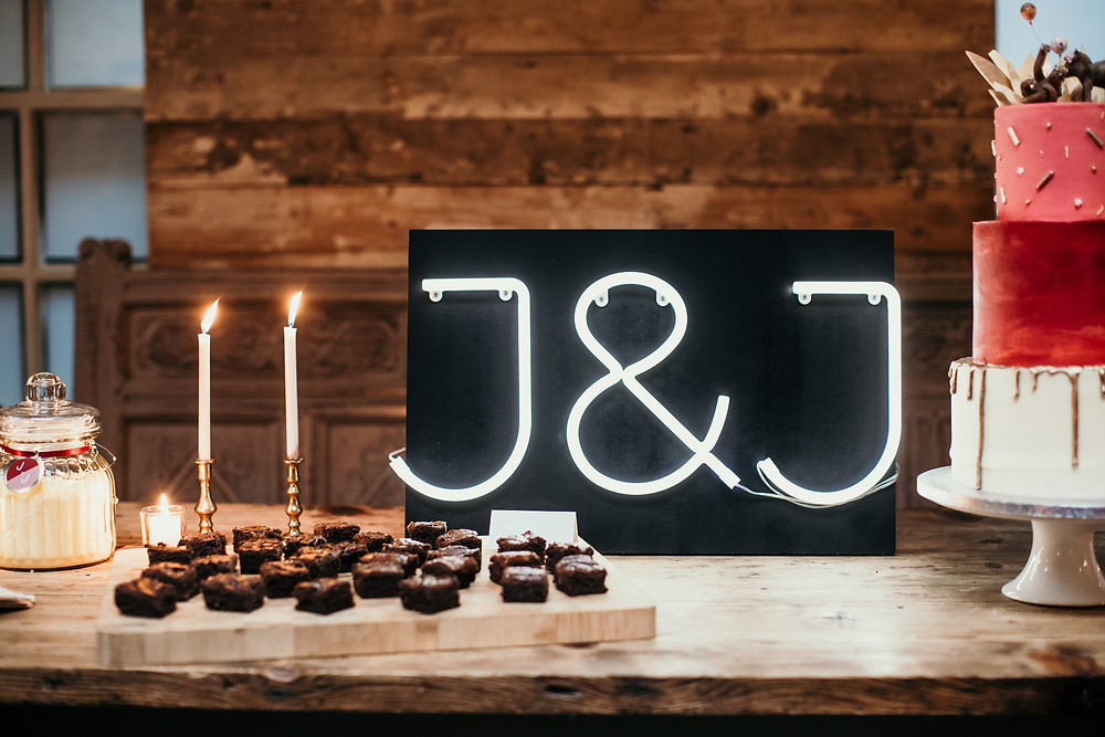 Wedding dessert table with brownies, cake and a neon sign
