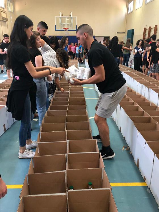 """תלמידי י""""ב 1 אורזים מזון למשפחות נזקקות"""