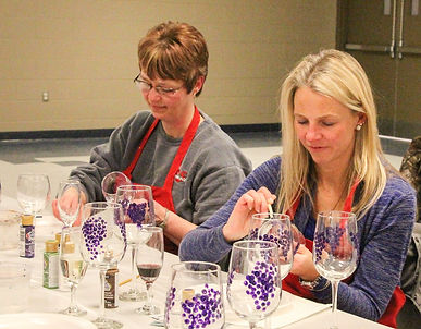 two women painting wine glasses in party situation