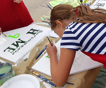 girl painting baseball sign PaintnPitchers