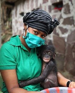 baby-bonobo-being-held-by-masked-caregiv