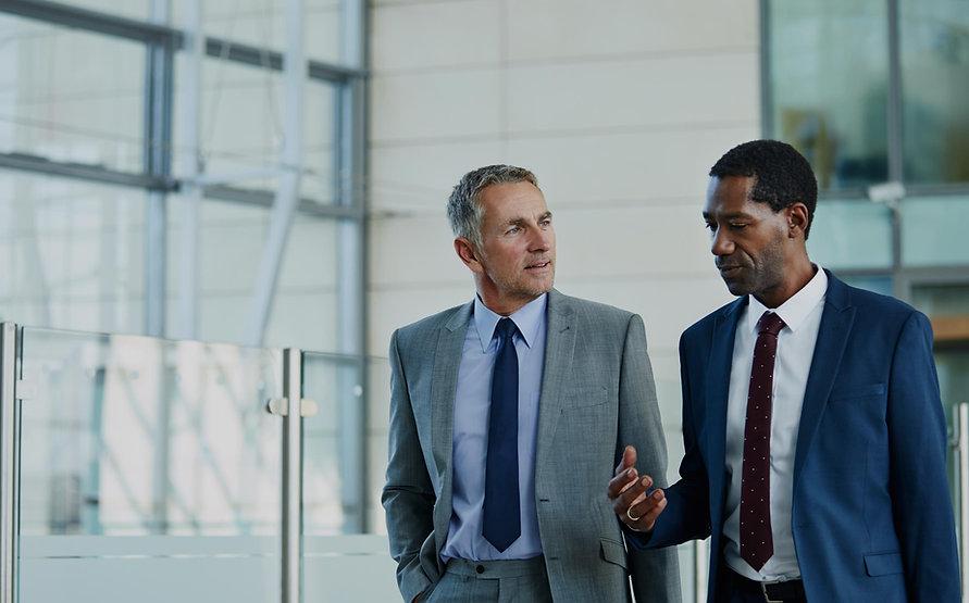 two-businessmen-walking-together-in-offi