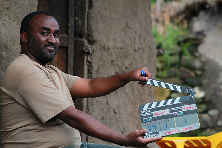 smiling-african-man-holding-a-film-clapp