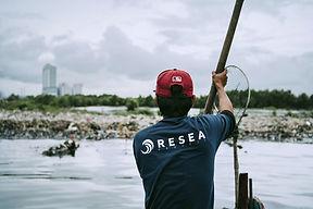 Fisherman-at-boat-looking-at-a-big-plastic-pile