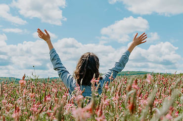 woman-in-a-field-of-flowers-holding-hand