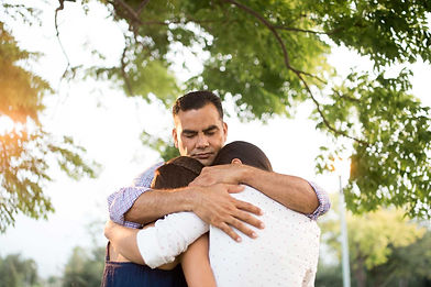 Grieving father hugging daughters