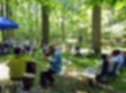 group-people-sitting-in-forest-listening