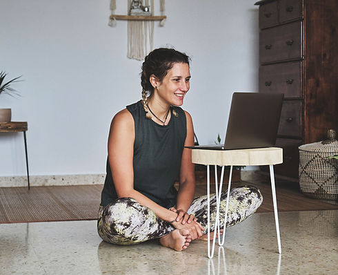 young-athletic-female-in-yoga-clothing-looking-at-computer-for-virtual-workout.jpg