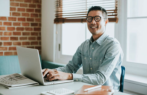 asian-american-man-sitting-at-desk-with-