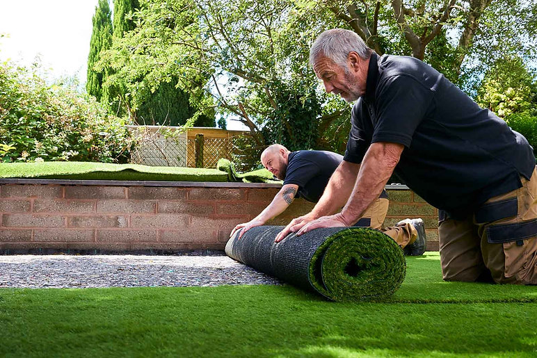 two-landscapers-rolling-out-grass-on-law