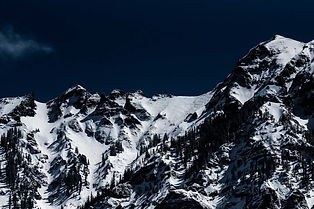 snow-covered-mountains-against-dark-blue