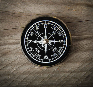 compass-lying-on-wood-table.jpg