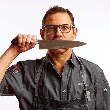 chef-john-tesar-holding-knife-to-his-mou