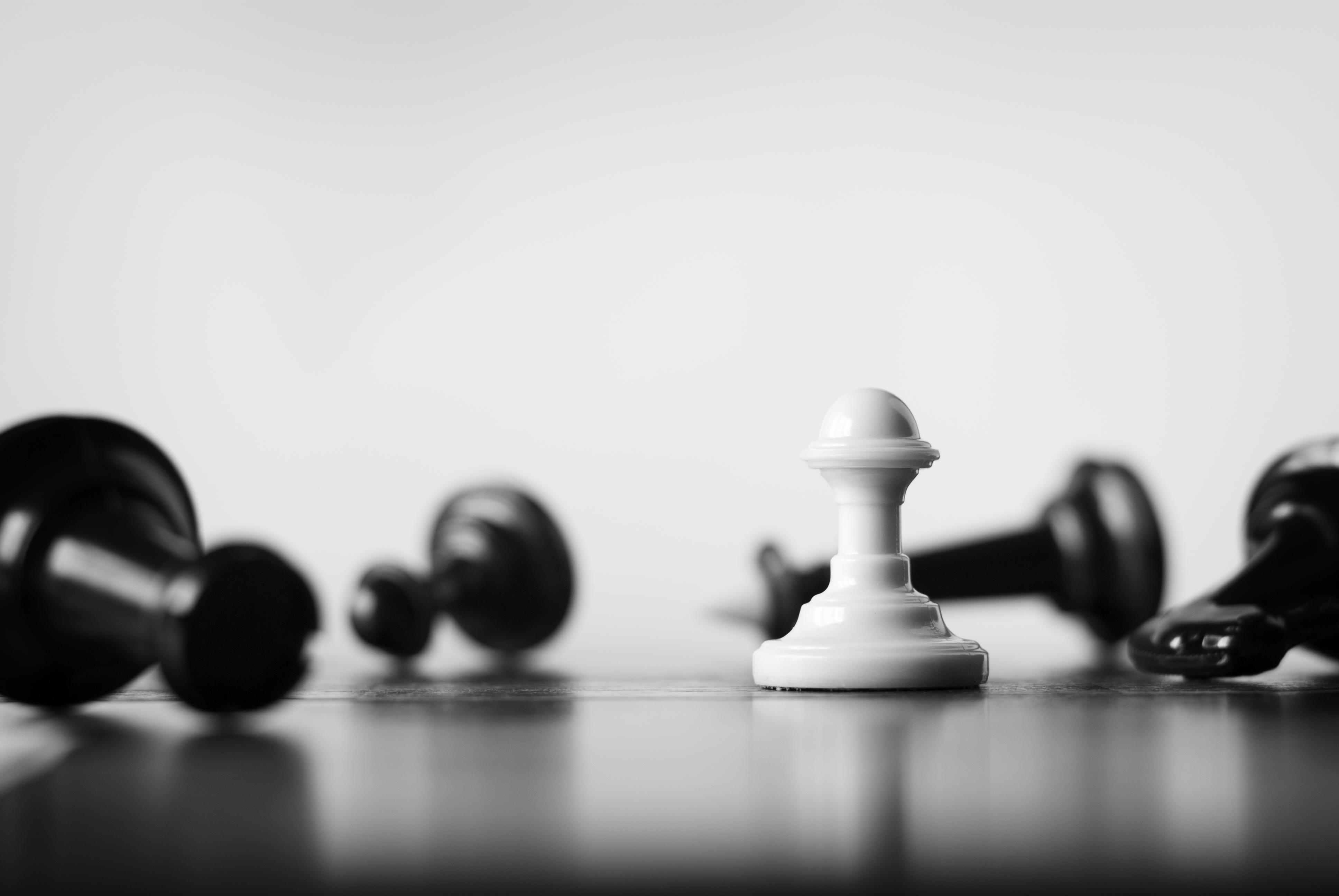 Single white pawn on a chess board surro